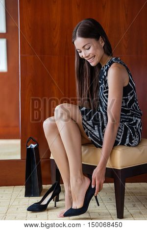 Woman trying on new expensive black high heels for elegant business outfit shopping at shoe store in mall or exclusive boutique. Asian girl at home happy of her online purchase putting fashion shoes.