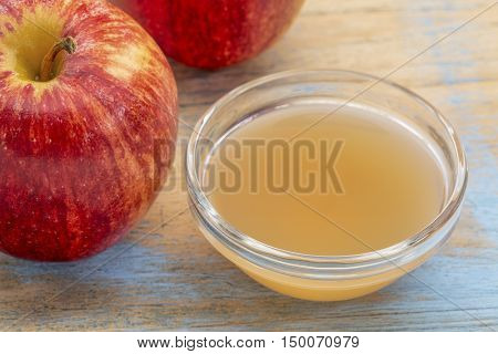 unfiltered, raw apple cider vinegar with mother - a small glass bowl with fresh red apples