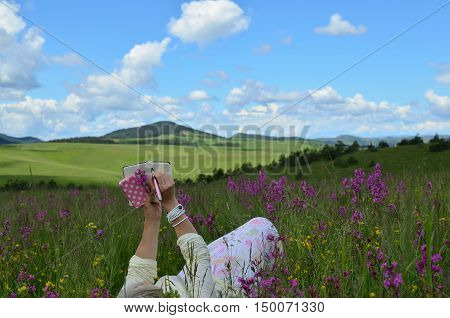 Woman lying on a spring field with wildflowers in beautiful landscape holding her cell phone and writing in her note pad
