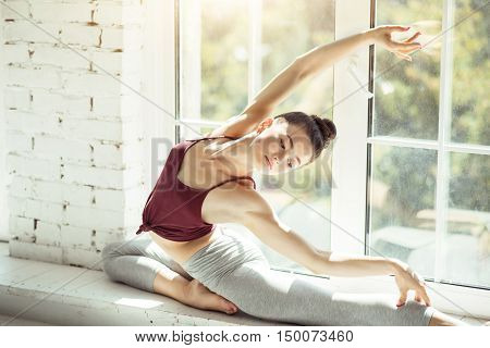 Beauty in movements. Elegant attractive slim lady holding her hand up and moving her body gracefully while sitting on a windowsill