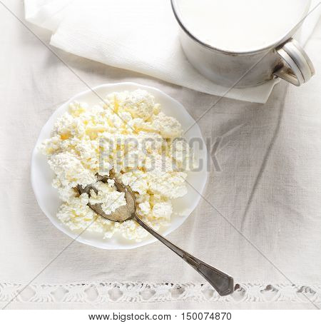 Dish of cottage cheese, a metal spoon and a mug of milk on a white background