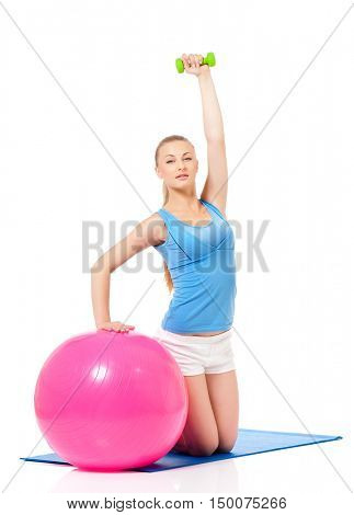 Young woman doing fitness exercise with gym ball and dumbbells, isolated on white background. Full lenght portrait of beautiful athlete girl in studio.