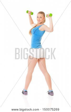 Young woman doing fitness exercise with dumbbells, isolated on white background. Full lenght portrait of beautiful athlete girl doing gym exercise in studio.