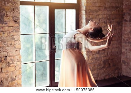 Feel the warmth. Charming elegant young dancer bending backwards and closing her eyes while enjoying the sunbeams
