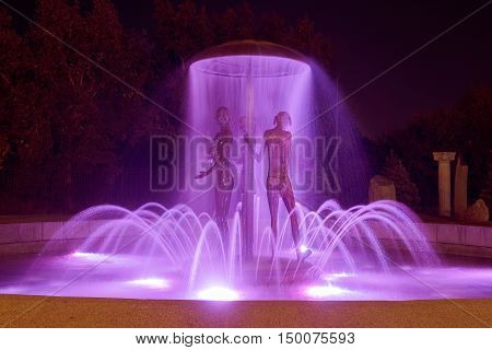 City fountain with colorful illumination at night with sculptures. Ukraine, Kiev. Travel entartainment sightseeing background