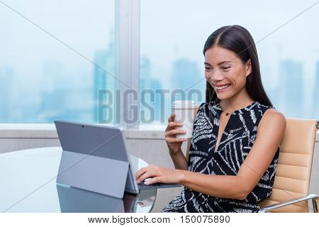 Happy young professional working typing on laptop drinking hot morning coffee cup on office desk. Asian business woman smiling surfing the web on work computer at office job with city skyline.