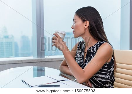 Office woman drinking coffee happy relaxing looking at city view through window. Beautiful Asian businesswoman taking a break from work thinking about career goal or pensive of job at business desk.