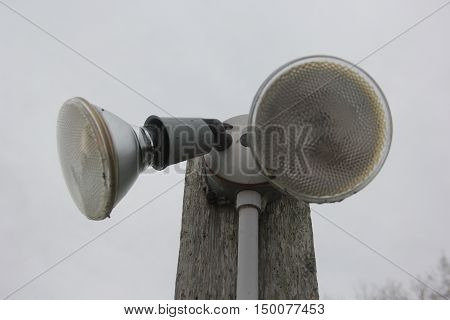 Two flood light outside on a post