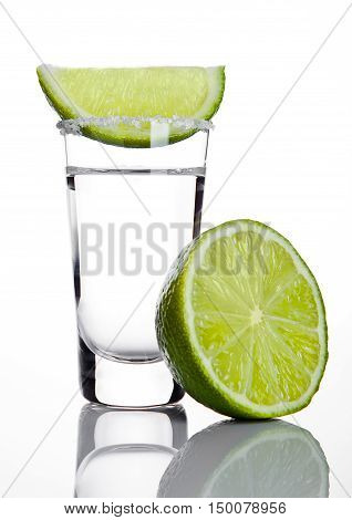 Silver tequila shot glass with lime slice and salt on white background
