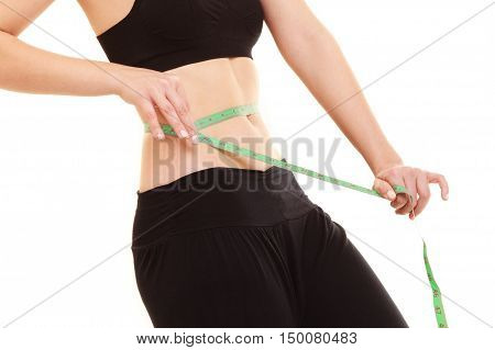 diet and healthy lifestyle. closeup of belly of slim fit girl young woman with green measure tape measuring her waist isolated on white