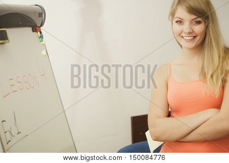 Education teaching and learning concept - Young smiling woman teacher standing near whiteboard