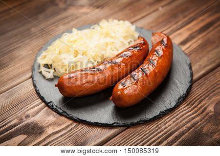 Bratwurst and sauerkraut on wooden table
