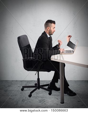 Businessman with puzzled expression looks at a hand-out from the computer screen