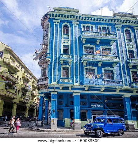 HAVANA - CUBA JUNE 10, 2016: Two men are painting a building on Monte Street in bright blue and yellow colors.