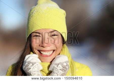 Winter season girl smiling having fun outside in snow. Portrait of Asian woman happy playful outdoors with healthy smile on sunny wintertime day wearing yellow outerwear beanie knit hat and gloves.