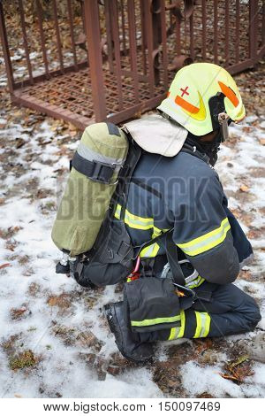 MOSCOW - DEC 17, 2014: Firefighter wearing helmet with oxygen cylinder in North Eastern Administrative District (Russian Emergency Situations Ministry)