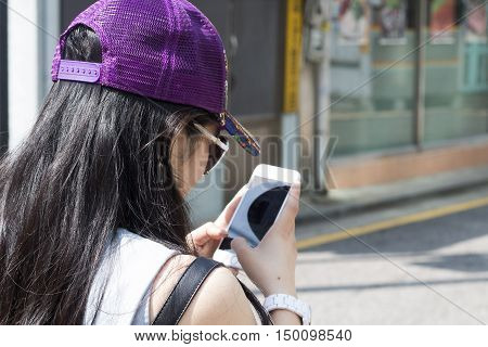 Asian girl using cell phone on a street under the sunlight