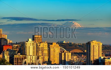 Mount Rainier looms over a portion of Seattle in evening sunlight