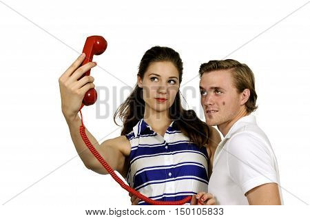 Woman and man trying to take a selfie with a rotary phone