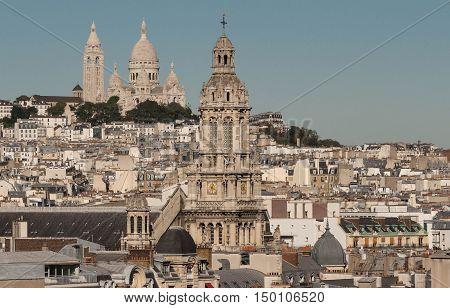 The Saint Trinity church and Sacre Coeur basilica and parisian houses in the background Paris France.