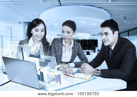 Group of Asian business team discussing in the office while looking at virtual financial graph on the laptop
