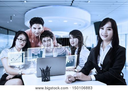Group of young business team smiling at the camera with virtual financial chart on the laptop computer shot in the office