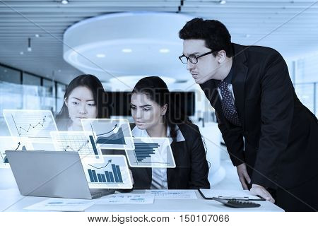 Group of multiethnic business people working with laptop computer and virtual chart in the office