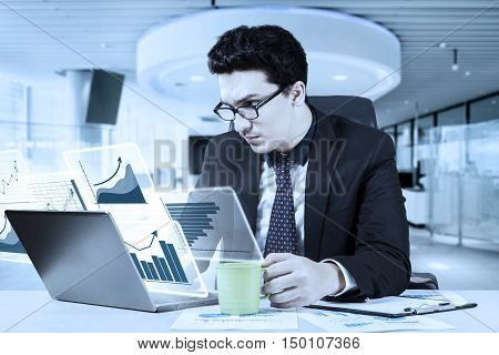 Photo of a busy Caucasian businessman working in the office with virtual financial graph on the laptop and holding a cup of coffee