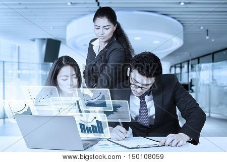 Group of three multiethnic business people in a business meeting with virtual chart on the laptop shot in the office
