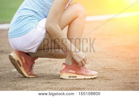 Young woman tying laces of running shoes before training