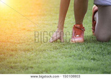 Runners feet on starting blocks in a athletic running track - Young multi race people training outdoor at sunset - Close up on shoe with back lighting - Soft warm filter with focus on first shoe