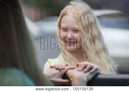 blonde mother in car and daughter near car saying goodbye