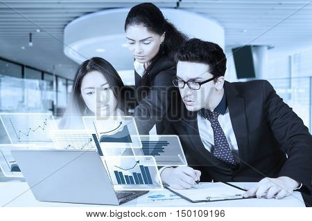 Image of three multiracial business people working together in the office with virtual graph on the laptop