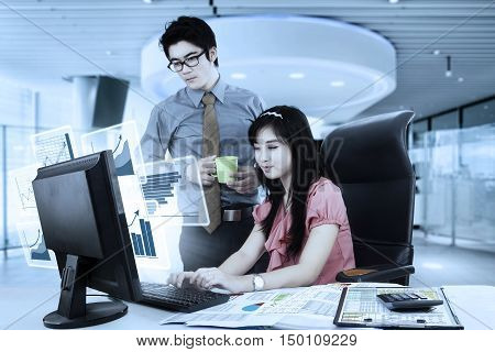 Photo of two young businesspeople working with virtual financial graph on the monitor shot in the office