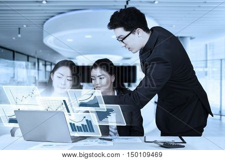 Group of multiethnic business team discussing together with laptop and virtual financial graph in the office