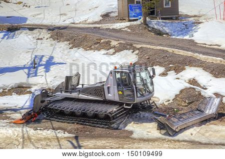 CAUCASUS RUSSIA - May 01.2015: Snow grooming on the shoulder of road on the of mount Everest
