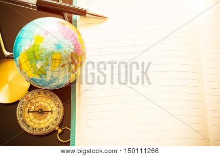 Travel concept pen compass globe and empty of notebook for for blog entries you can place your text or information. Top view. Vintage filtered.