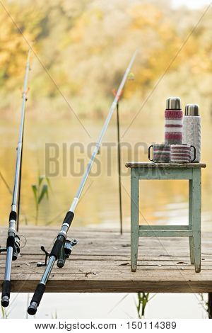 Fishing on the river. A fishing rod and a thermos with cups in knitted covers.