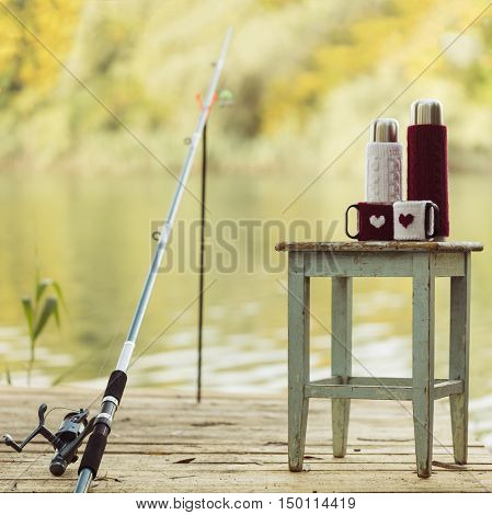 Fishing on the river. Fishing rod and a thermos Cup in a knitted cover pattern - heart.