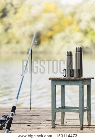 Fishing on the river. A fishing rod and a thermos with cups.
