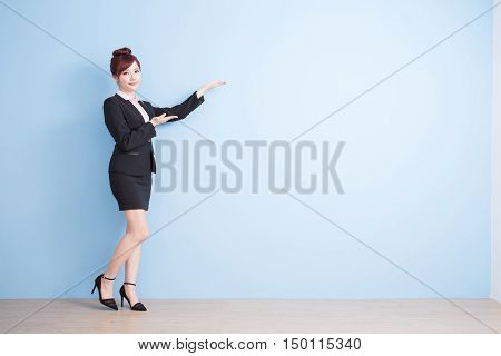 business woman is smile and show something to you with blue background asian