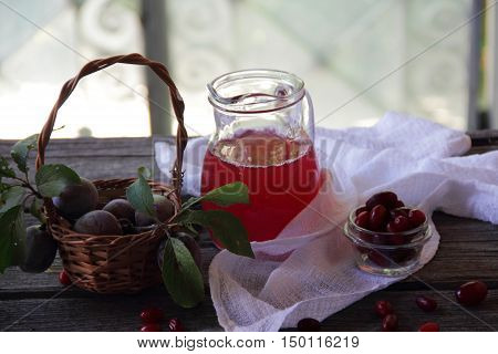 compote of dogwood and fresh plums in basket on wooden table