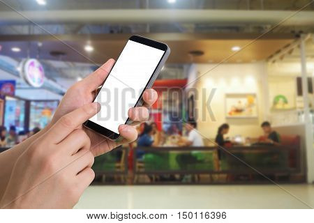 human hand hold and touch smartphone tablet cell phone with blank screen on blurred people eating at food court background.