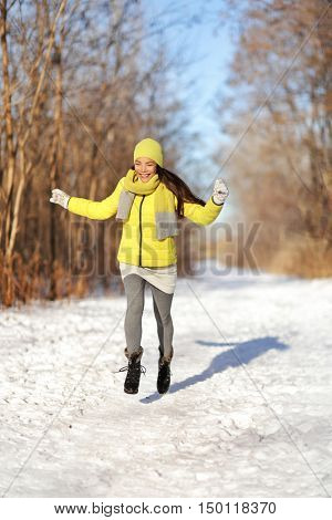 Happy girl running in snow winter landscape. Joyous young Asian woman having fun walking in nature forest park on snowy path wearing yellow outerwear with warm accessories: boots, gloves, hat, scarf.
