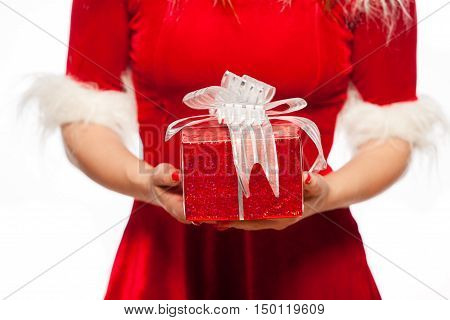 christmas, x-mas, winter, happiness concept - Time gifts - gift box in hand girls in santa helper hat, over red background.