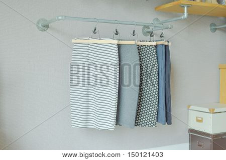 skirts hanging on industrial style clothes rail in walk in closet