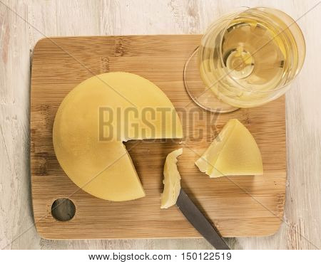 A photo of tetilla, a traditional Spanish soft cow milk cheese, with a slice cut off, and a glass of white wine, shot from above on a wooden board