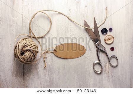 A photo of vintage scissors with a roll of twine, a tag with copyspace, and buttons, shot from above on light wooden boards background texture