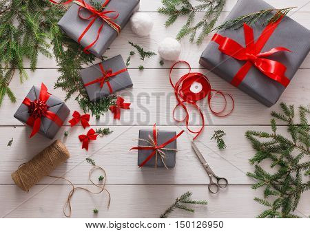 Creative diy hobby. Giftwrapping. Wrapping modern christmas present, boxes in stylish gray paper with red ribbon. Top view of messy white wooden table with fir tree branches, decoration of gift.