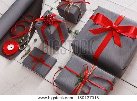 Gift wrapping. Packaging modern christmas present. Lots of gift boxes in stylish modern gray paper, decorated with red satin ribbon bows. Christmas and winter holidays concept